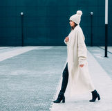 Fashionable stylish looker girl in white cap and knit coat. Walks on the street. Outdoor. Streetstyle. Stock Images