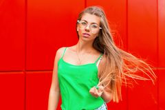 Fashionable stylish portrait of a beautiful woman. With sunglasses in the bright green blouse near the red wall royalty free stock photo