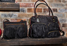 fashionable, stylish woman black bags, purse standing on wooden shelf against old brick background Royalty Free Stock Photos