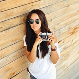 Fashionable stylish woman with old camera wearing sunglasses Stock Image
