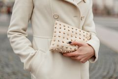 Fashionable stylish women`s handbag in women`s hands. On the street royalty free stock images