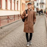 Fashionable stylish young guy in a vintage fashion coat with. A cap with sneakers and bag posing in the city Stock Photography