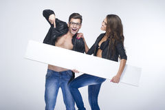 Fashionable surprised couple holding  board Stock Photos