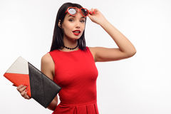 Fashionable surprised young lady in a red dress and clutch holds on to sunglasses in the shape of a heart Royalty Free Stock Image