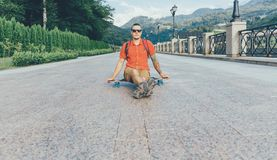 Guy sitting on longboard outdoor. Fashionable tattoed guy in sunglasses sitting on longboard outdoor Royalty Free Stock Images