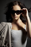 Fashionable teen in sunglasses. Half body portrait of fashionable female teenager in sunglasses, dark studio background Royalty Free Stock Photography