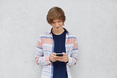 Fashionable teenage boy wearing shirt, holding cell phone in hands, messaging with friends or playing games online using free inte. Rnt connection. Teenager with Royalty Free Stock Photos