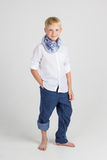 Fashionable teenager boy in blue scarf smiles Royalty Free Stock Images