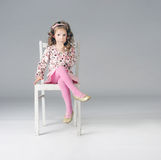 Sweet thoughtful little girl sitting on the white chair, a lot o. Fashionable thoughtful little girl posing on the white chair, looking away. Long curly hair Royalty Free Stock Photography