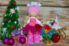 Fashionable Tilda doll made of synthetic winterizer on the background of Christmas decorations and wooden background. royalty free stock photos