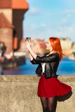 Fashionable tourist girl taking picture with camera old town Gdansk Royalty Free Stock Photography