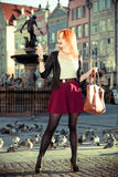 Fashionable tourist girl taking picture herself camera old town Gdansk Royalty Free Stock Photo
