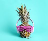 Fashionable trendy pineapple fruit with headphones and sun glasses listen to the music over bright pastel cyan background. Cool hipster ananas with funny face stock photos