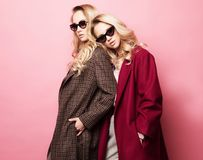Fashionable two blond women in coat with sunglasses. Fashion autumn winter photo. Fashionable two blond women in coat with sunglasses posing on pink background Royalty Free Stock Photos