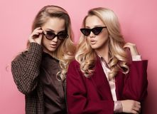 Fashionable two blond women in coat with sunglasses. Fashion autumn winter photo. Fashionable two blond women in coat with sunglasses posing on pink background Stock Photos