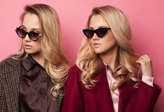 Fashionable two blond women in coat with sunglasses. Fashion autumn winter photo. Fashionable two blond women in coat with sunglasses posing on pink background Royalty Free Stock Photo