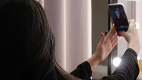 Woman takes a selfie. Fashionable unrecognizable young woman takes a selfie with her phone on the background of lights. A girl makes a photo on a smartphone stock footage