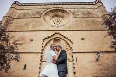 Fashionable wedding couple near Catholic church. Bride and Groom. Outdoor portrait royalty free stock photography