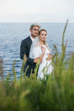 Fashionable wedding couple near ocean. Bride and Groom. Outdoor portrait Stock Image