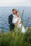 Fashionable wedding couple near ocean. Bride and Groom. Outdoor portrait Stock Photography