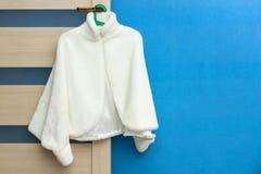 Free Fashionable White Female Coat Hanging On Door Handle On Blue Wall Background Stock Image - 171810271