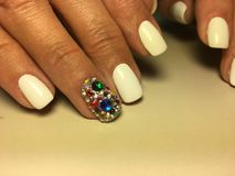 Fashionable manicure with colored rhinestones on a textural background royalty free stock photo