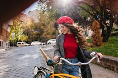 Fashionable white woman looking down with smile, holding bicycle in beautiful park. Stylish lady with long curly hair