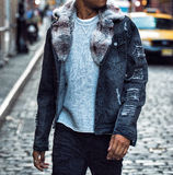 Fashionable winter jeans coat with fur and cuts on male model walking on city street. Stock Photos