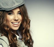 Fashionable woman. In a hat posing in light background Royalty Free Stock Photography