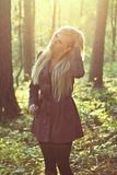 Fashionable woman. Blonde in a coat in the woods and compares her hair Royalty Free Stock Photos
