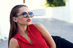Fashionable woman. Beautiful stylish girl in red blouse and sunglasses Royalty Free Stock Photo
