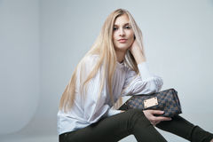 Fashionable woman with a bag in light background. Full length casual young fashionable woman with a bag in light background stock image