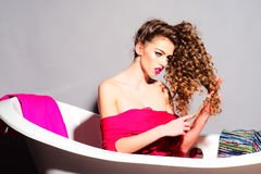 Fashionable woman in bathtub. Young beautiful fashionable woman with curly hair in pink clothes sitting in bathtub Stock Image