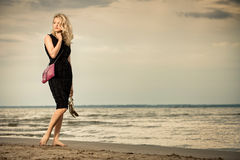 Fashionable woman on beach. Fashionable young woman in dress with handbag paddling on sandy beach Royalty Free Stock Photography