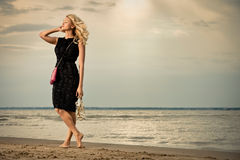 Fashionable woman on beach. Fashionable young woman in dress with handbag paddling on sandy beach Royalty Free Stock Photo