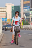 Fashionable woman on a bicycle, Beijing downtown, China Royalty Free Stock Photos