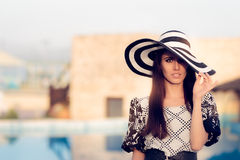 Fashionable Woman with Big Summer Hat by The Pool Royalty Free Stock Image