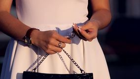 Fashionable woman with a black bag in her hands stock footage