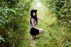 Fashionable woman in black hat sitting in green forest Stock Photography