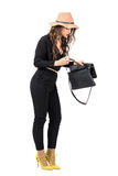 Fashionable woman in black overalls searching for something lost in her handbag Royalty Free Stock Photos