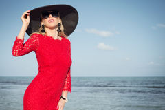 Fashionable woman with black summer hat and red dress on the beach Stock Image