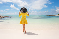 Fashionable woman with black summer hat and yellow dress on the beach royalty free stock images