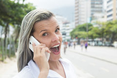 Fashionable woman with blonde hair at phone in the city Stock Images