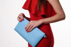 Fashionable woman with a blue bag and red evening dress Royalty Free Stock Images