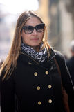 Fashionable woman with coat, bag, scarf and sunglasses Royalty Free Stock Image
