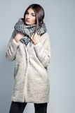 Fashionable woman in coat, woolen scarf and hat posing in studio over grey background. Royalty Free Stock Photography