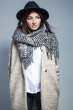 Fashionable woman in coat, woolen scarf and hat posing in studio over grey background. Stock Images