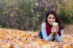 Fashionable woman with coffee lying down on fall leaves Stock Image