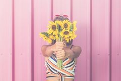 ee08e3ca8a Fashionable woman covering her face with sunflowers against rose wall.  Hipster girl holding bouquet of