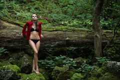 Fashionable woman in dark forest near river Royalty Free Stock Image